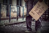 Poverty concept. Poor man holding cardboard sheet with text I NEED HELP on street poster