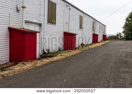 Abandoned Old Warehouse Building With Red Outcroppings By A Road