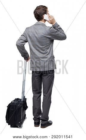 Back view of business man with suitcase talking on the phone. Standing young girl. Rear view people collection.   Isolated over white background. Young traveler with a suitcase talking on white phone