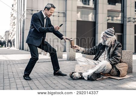 Vain Rich Man Making Selfie Of Himself With Dirty Homeless