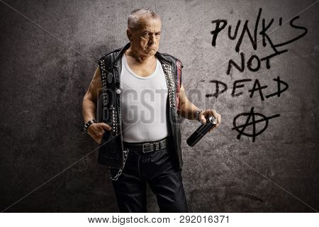 Mature male punker holding a wall spray and leaning against a rusty gray wall with text punk's not dead and anarchy sign