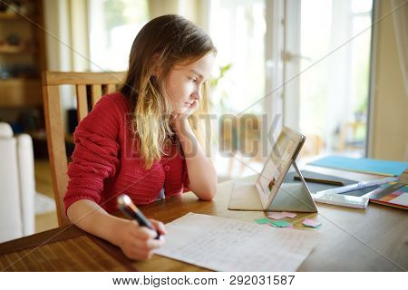 Smart Preteen Schoolgirl Doing Her Homework With Digital Tablet At Home. Child Using Gadgets To Stud