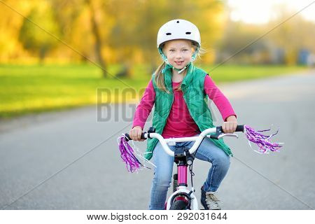 Cute Little Girl Riding A Bike In A City Park On Sunny Autumn Day. Active Family Leisure With Kids.
