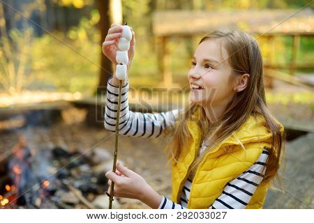 Cute Preteen Girl Roasting Marshmallows On Stick At Bonfire. Child Having Fun At Camp Fire. Camping