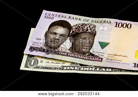 One Thousand Nigerian Naira Bank Note On A Us Dollar Note. Foreign Exchange And Trade.