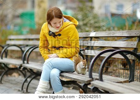 Happy Young Woman Tourist Feeding A Squirrel In Madison Square Park, New York City, At Sunny Spring