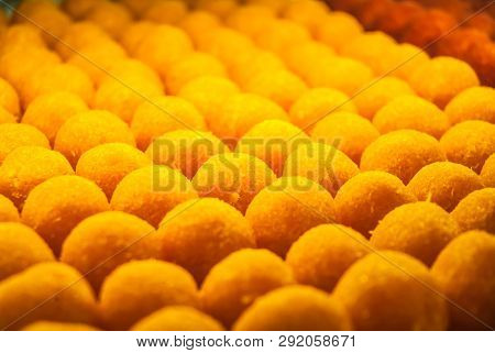 Close Up Of Sweet Yellow Balls With Orange Flavour Displayed In Patisserie