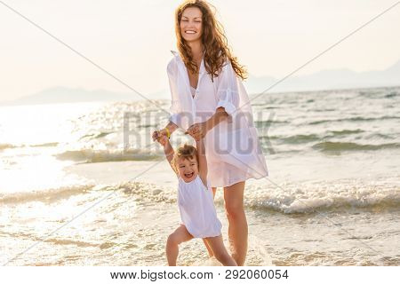 Mother and little daughter playing on the sea beach in Greece