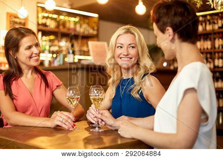 people, celebration and lifestyle concept - happy women drinking wine and talking at bar or restaurant