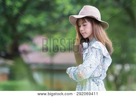 Beautiful Asian Woman Relaxing By Reading Book In Park