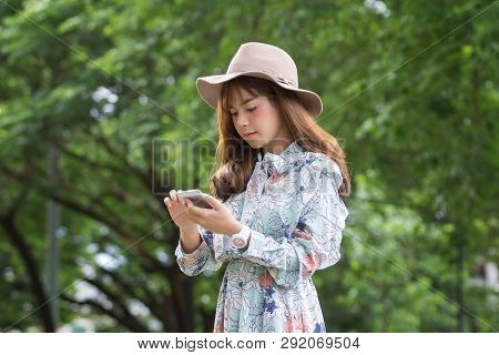 Beautiful Asian Woman Relaxing By Using Smartphone In Park