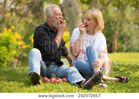 Happy Senior Couple Relaxing In Park Eating Apple Together Morning Time. Old People Sitting On Grass