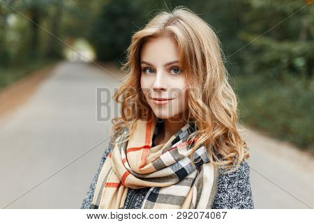 Cute Attractive Pretty Young Woman With Blue Eyes With Natural Make-up In A Stylish Coat In A Beige