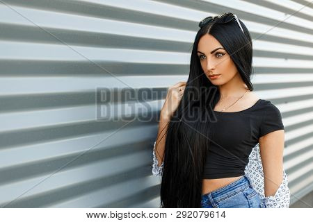 Beautiful Pretty Modern Young Brunette Woman With Long Hair In Vintage Jeans In A Stylish Black Top