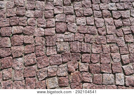 Paving Stone Laid Out Of Square Granite Stones Of Brown Color. Stones With Jagged Edges. The Texture