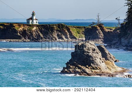 Rock Cliffs, Blue Water And The Cape Arago Lighthouse On The Picturesque Pacific Coast Of Oregon.