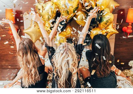 Women Night Out. Party Leisure Time. Females On Bed Catching Glitter Confetti And Balloons. Youth Jo