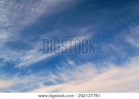The Sky With Light Feathery White Clouds Lit By The Rays Of The Sun