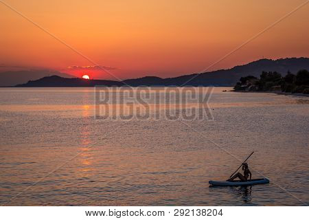 Silhouette Of Young Girl On Sup Surf In The Water At Sunset