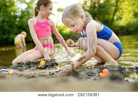 Two Little Sisters Having Fun On A Sandy Lake Beach On Warm And Sunny Summer Day. Kids Playing By Th