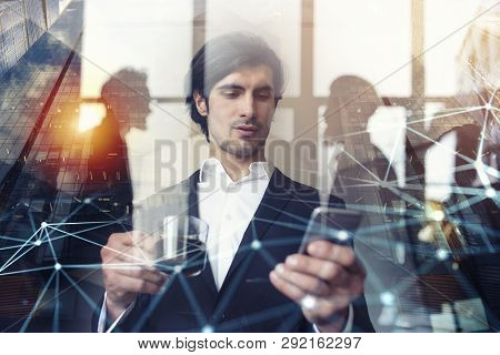 Businessman Works With His Smartphone In Office. Double Exposure.