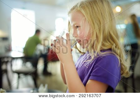 Cute Little Girl Drinking Water On Hot Summer Day. Child Holding A Glass Of Water.