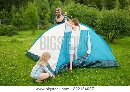 Cute Little Girls Helping Their Parent To Set Up A Tent On A Campsite. Active Lifestyle, Family Recr