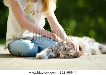 Cute Young Girl With Her Cat On Sunny Autumn Day. Adorable Child Petting Her Kitty. Kids And Animals