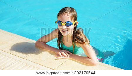 Cute Young Girl Wearing Swimming Goggles Having Fun In Outdoor Pool. Child Learning To Swim. Kid Hav