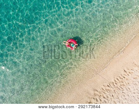 Aerial Top Down View Of Cute Young Girl Floating On Toy Ring At Myrtos Beach, The Most Beautiful Bea