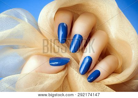 Female Hand With Dark Blue Nails Is Holding A Beige Decoration On Blue Background, Manicure And Nail