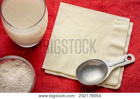 food grade diatomaceous earth supplement - powder and in a glass of water with a measuring spoon and a napkin