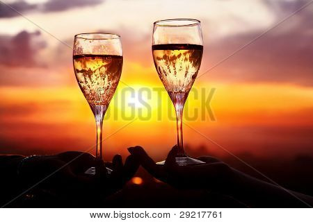 Man and woman clanging wine glasses with champagne at sunset dramatic sky background poster