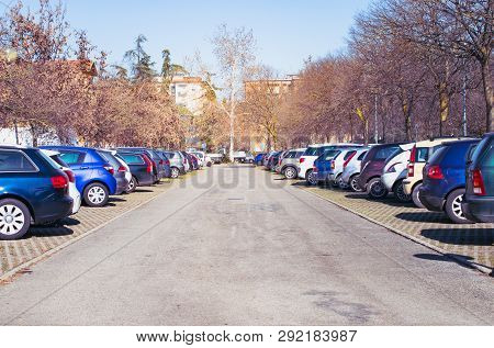 Outdoor Parking Lot With Car Parking In Large Asphalt Parking Lot With Autumn Trees.