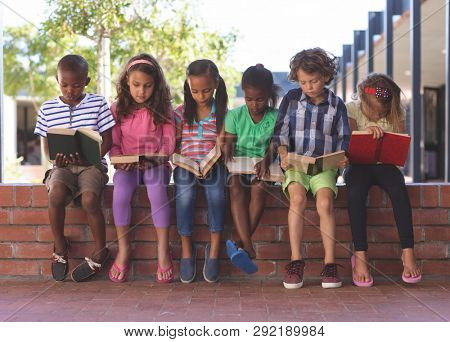 Front view of multi ethnic students reading book while sitting on brick wall at corridor in school