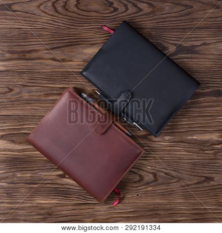 Black And Brown Handmade Leather Notebook Cover With Notebooks And Pen On Wooden Background. Stock P