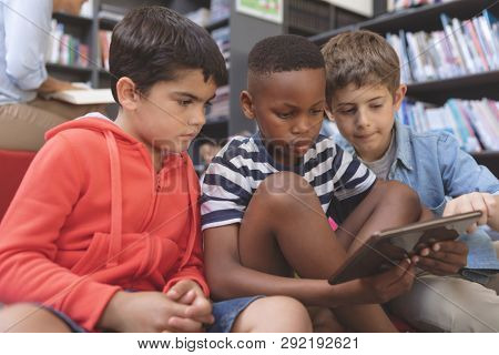 Side view of schoolboys using a digital tablet while they are sitting on cushions in a library at school with their teacher reading a story to their classmates in background
