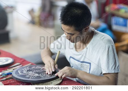 Dunhuang, China - 08 06 2016: A Craftsman Depicts Dunhuang Culture Through Wood Carvings. A Chinese