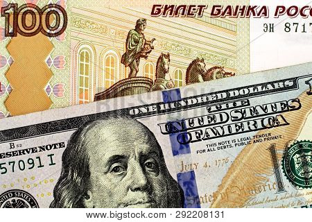 A Close Up Image Of A New, American One Hundred Dollar Bill With A One Hundred Russian Ruble Note In