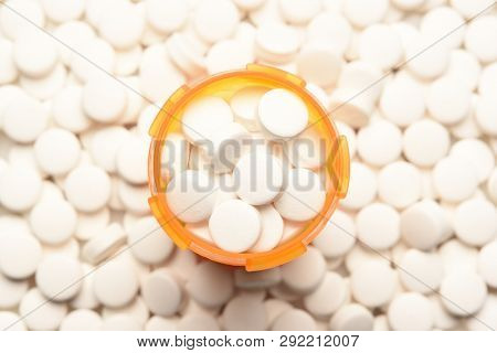Opioid Crisis Concept: High angle view of a prescription bottled filled with pills surrounded by more of the same tablets.