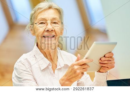Senior woman in retirement home has fun social media with tablet computer