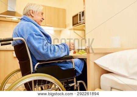 Senior in a wheelchair at breakfast in the senior citizen apartment in the senior residence