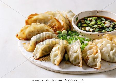 Fried Asian Dumplings Gyozas Potstickers In White Ceramic Plate Served With Bowl Of Soy Onion Sauce