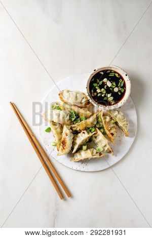 Fried Asian Dumplings Gyozas Potstickers In White Ceramic Plate Served With Chopsticks And Bowl Of S