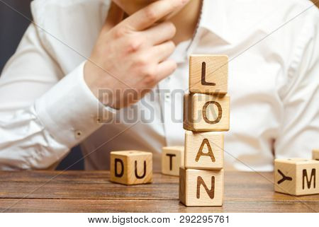 Wooden Blocks With The Word Loan And Businessman. Consumer, Banking And Property Loan. Business And