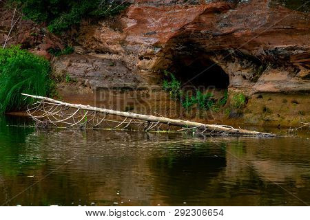Closeup Of Sandstone Cliff Formation With Cave On Bank Of River Gauja In Latvia. Log In The River Ne