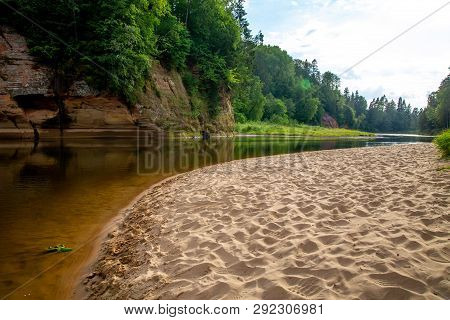 Landscape Of Cliff With Cave Near The River Gauja, Sandy Shore And Forest In The Background. The Gau