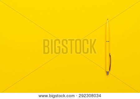 Ballpoint Pen On The Yellow Background. Photo Of Yellow Ballpoint Pen With Copy Space. Minimalist Sh