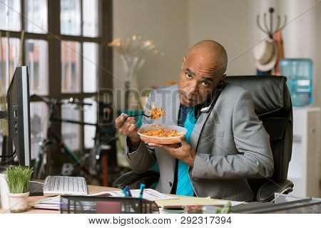 Professional Man On The Phone Eating At His Desk