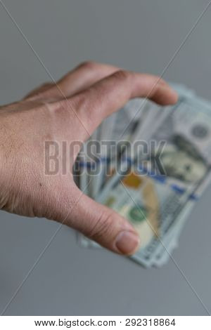 Hand Reaching For Dollars On Gray Background. Vertical Photo